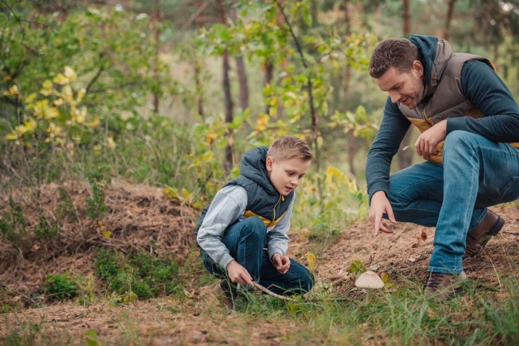 a dad and a boy in the woods looking for letterboxing treasure