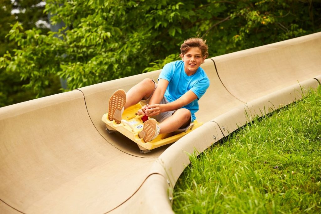 A teen boy smiling as he zooms down a mountain coaster in the summer time