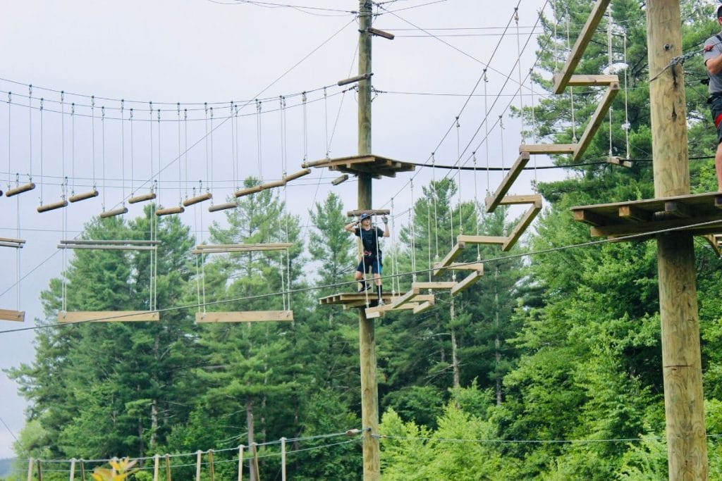 Teen boy on a wooden aerial ropes course at Boundless Adventures in Berlin, MA