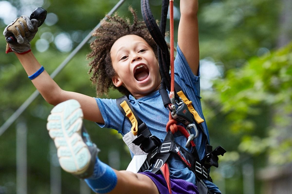 boy with harness on a rope course with a big smitle