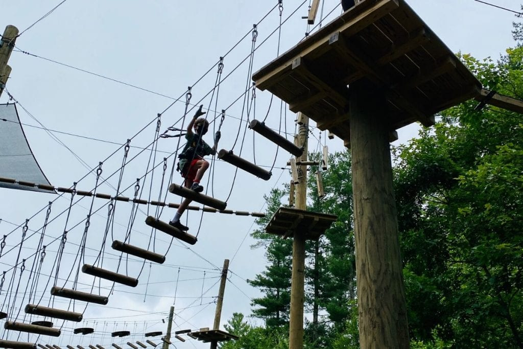 A young boy on an aerial rope course high over head climbing up higher to a platform