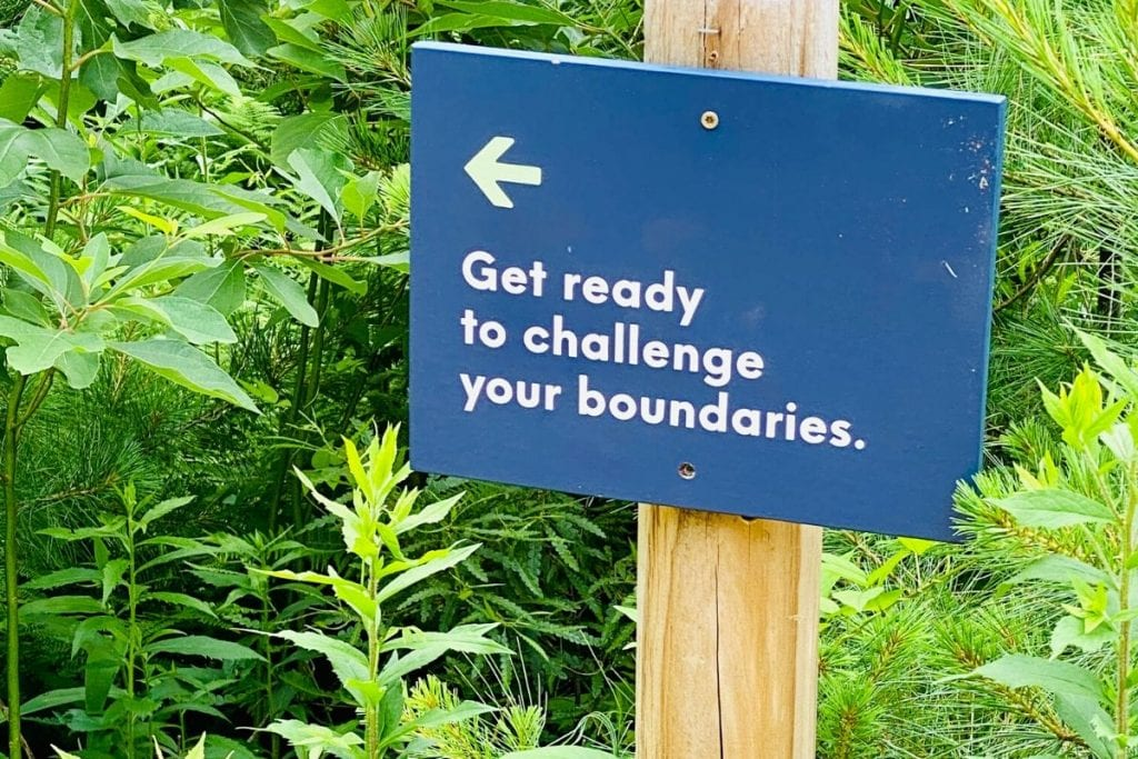 A sign that reads 'Get ready to challenge your boundaries' and an arrow pointing to the left