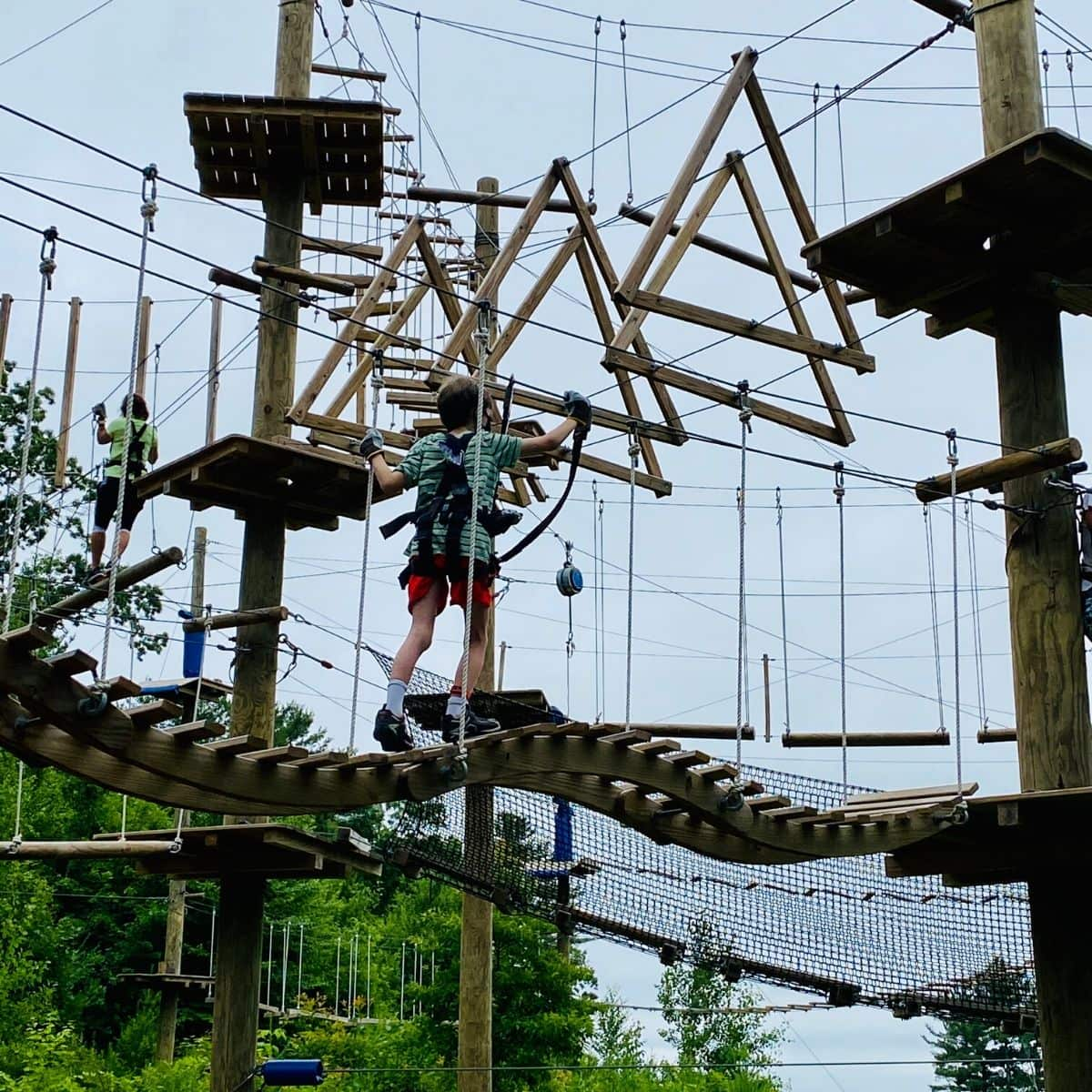 tween boy with a harness on balancing on a rope course