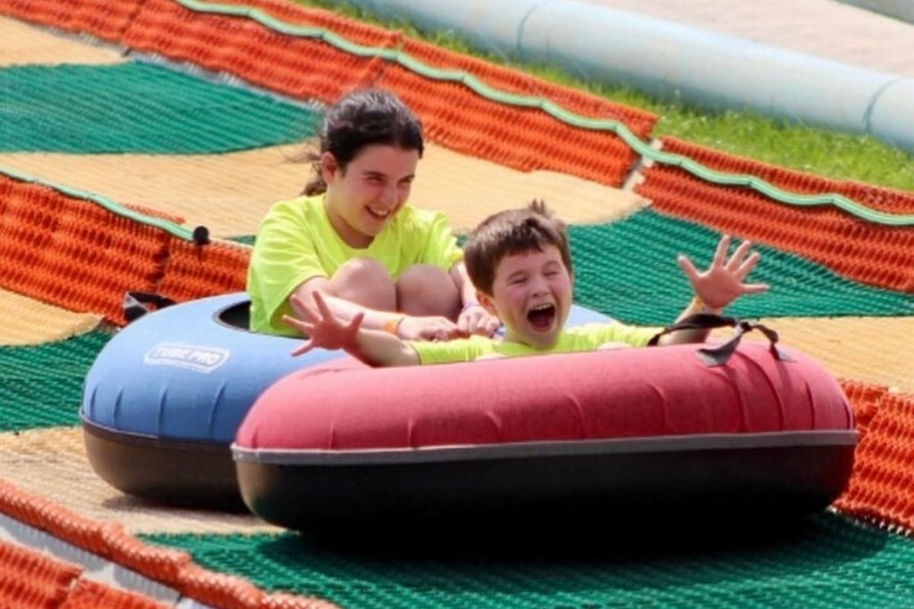 Two happy kids yelling as they zoom down in an inner tube