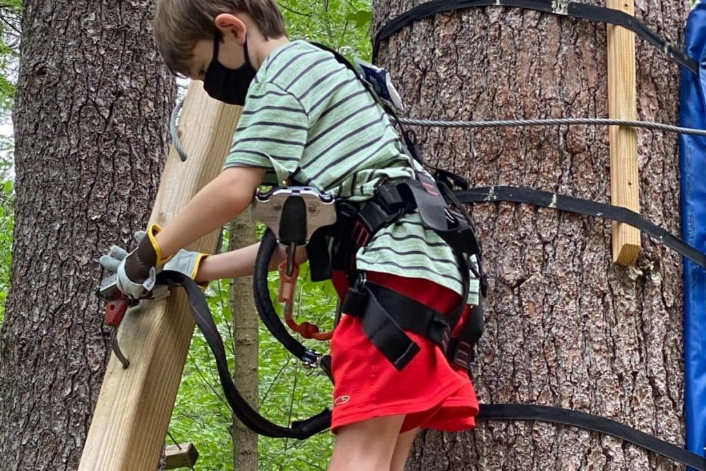 A tween aged boy releasing his clip at the end of the rope course upon completion at Boundless Adventures in Berlin, MA