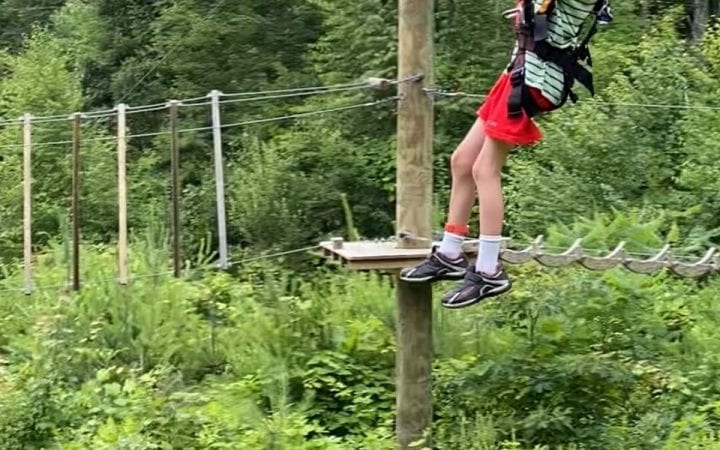 A child zip lining on a rope course