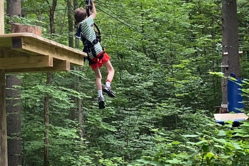 An 8-year old boy on a zip line aerial obstacle through the trees