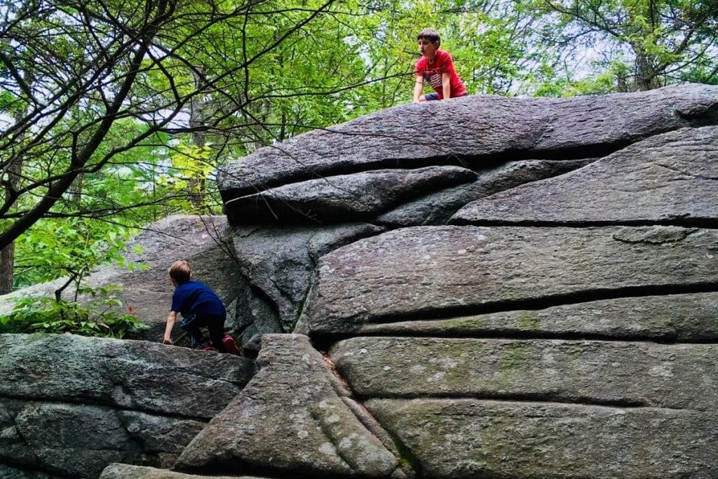 Two boys climbing up a huge boulder