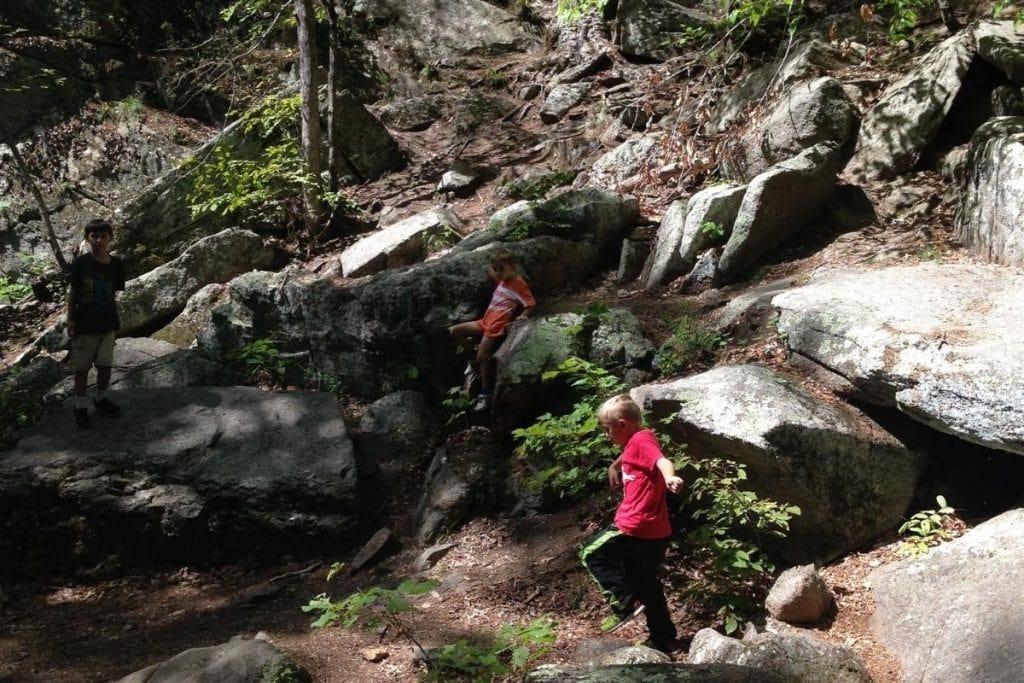 Kids having fun through a rocky chasm hike