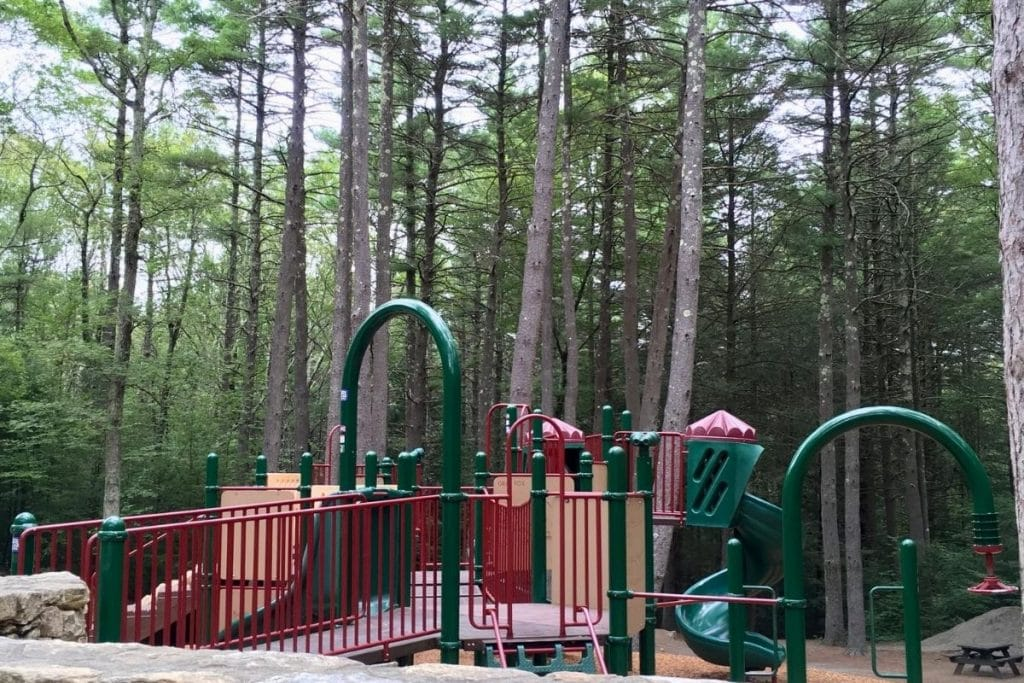 A green and red playground with climbing structures