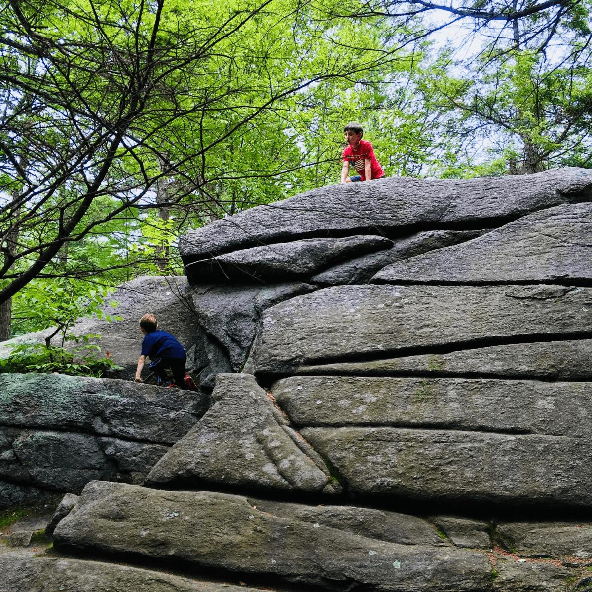 Kids climbing up a large boulder while hiking