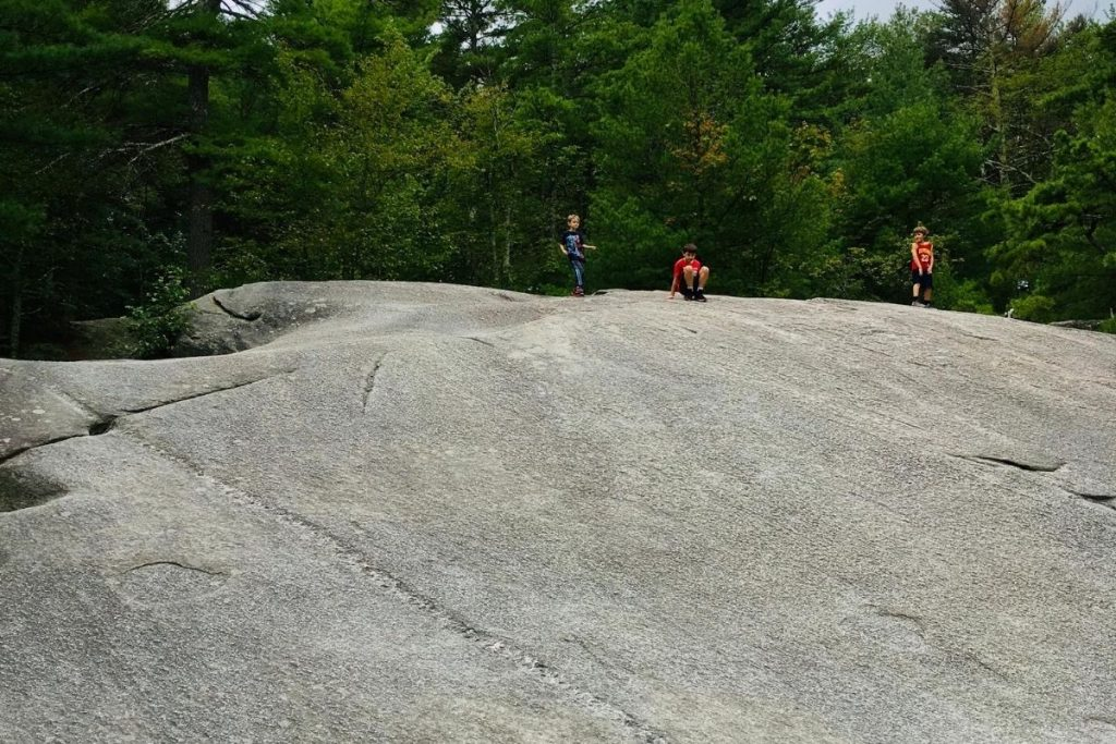 Kids on a large slanted rock, sitting on their butt and sliding down for fun