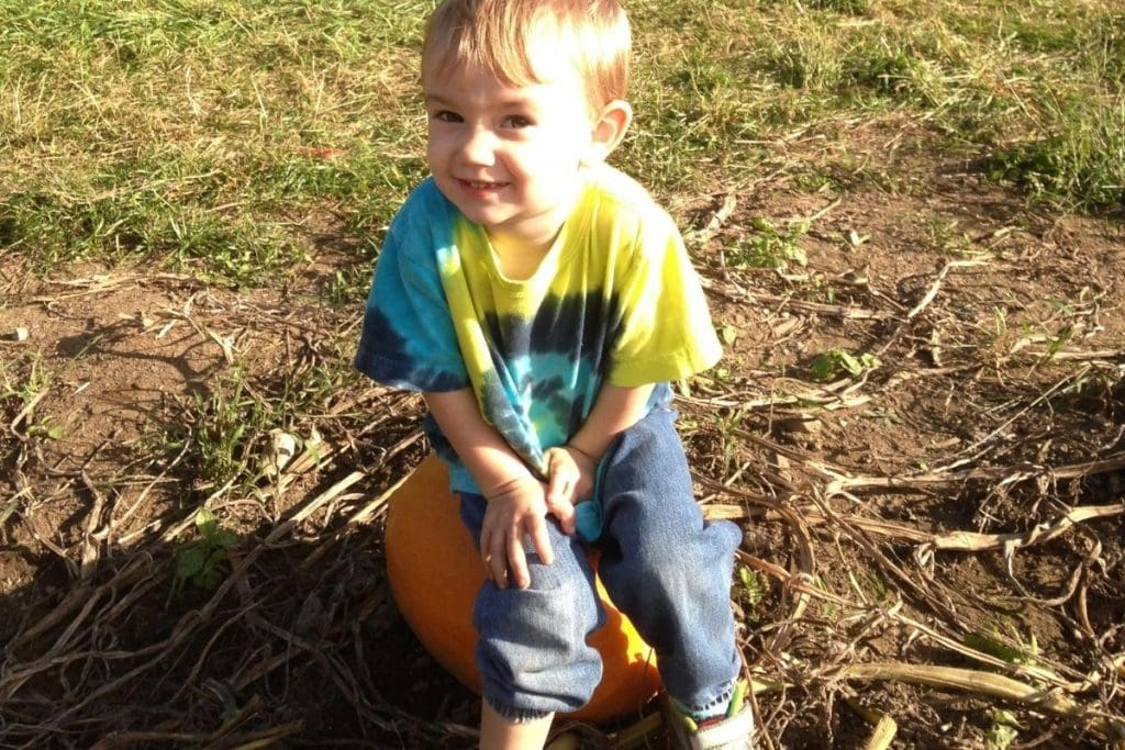 A young boy sitting on an orange pumpkin in a hay field