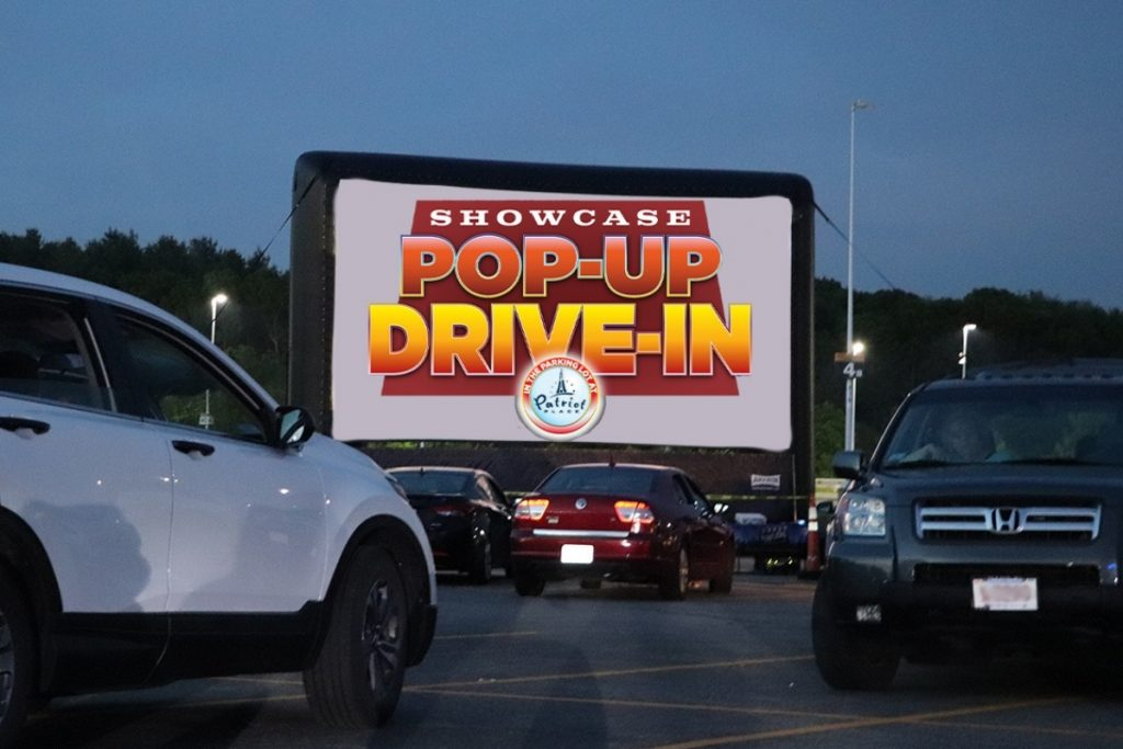 Cars at night parked in front of a drive in movie theatre