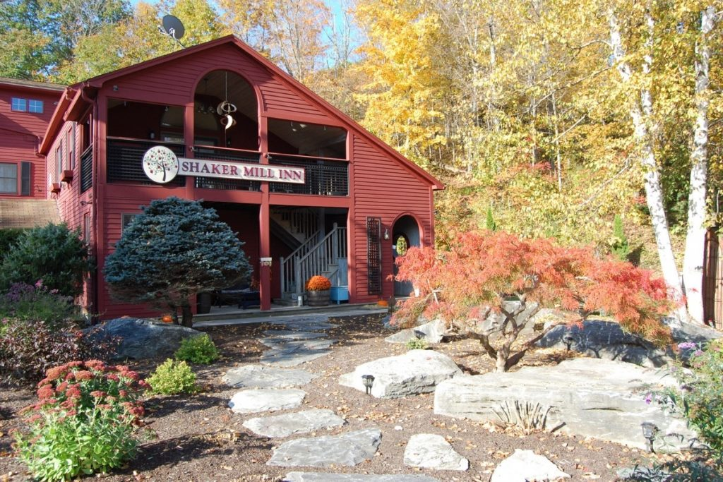 The red building of the Shaker Mill Inn in the fall time - fun for a weekend in the Berkshires