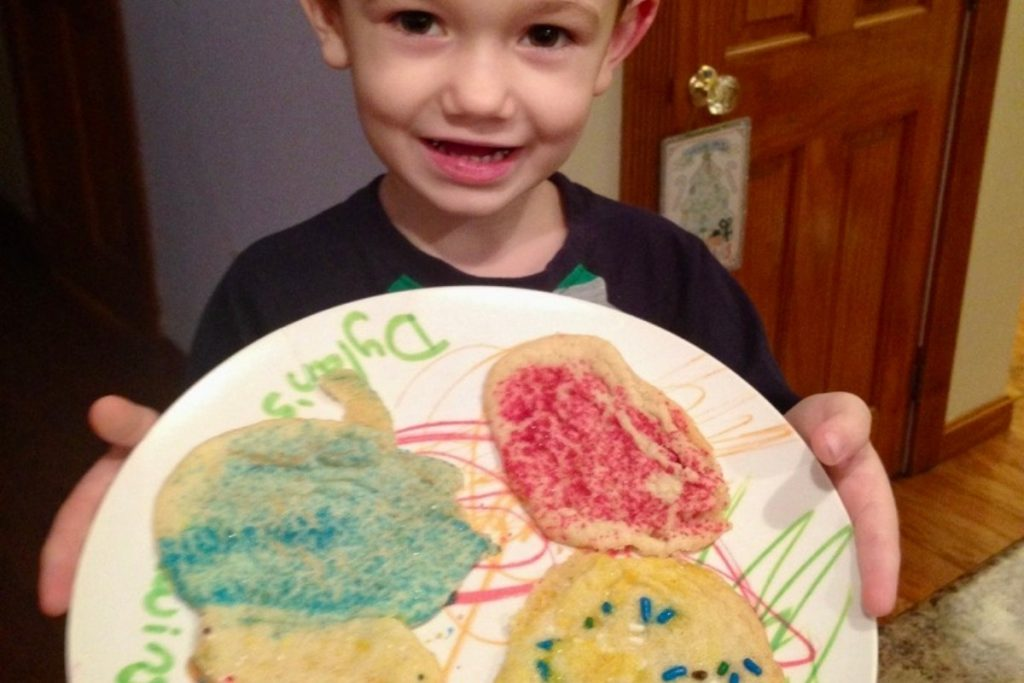 little boy holding a plate of hand decorated sugar cookies
