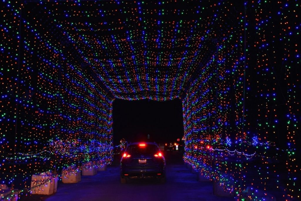 A car driving through a festive holiday light tunnel during the Christmas season.