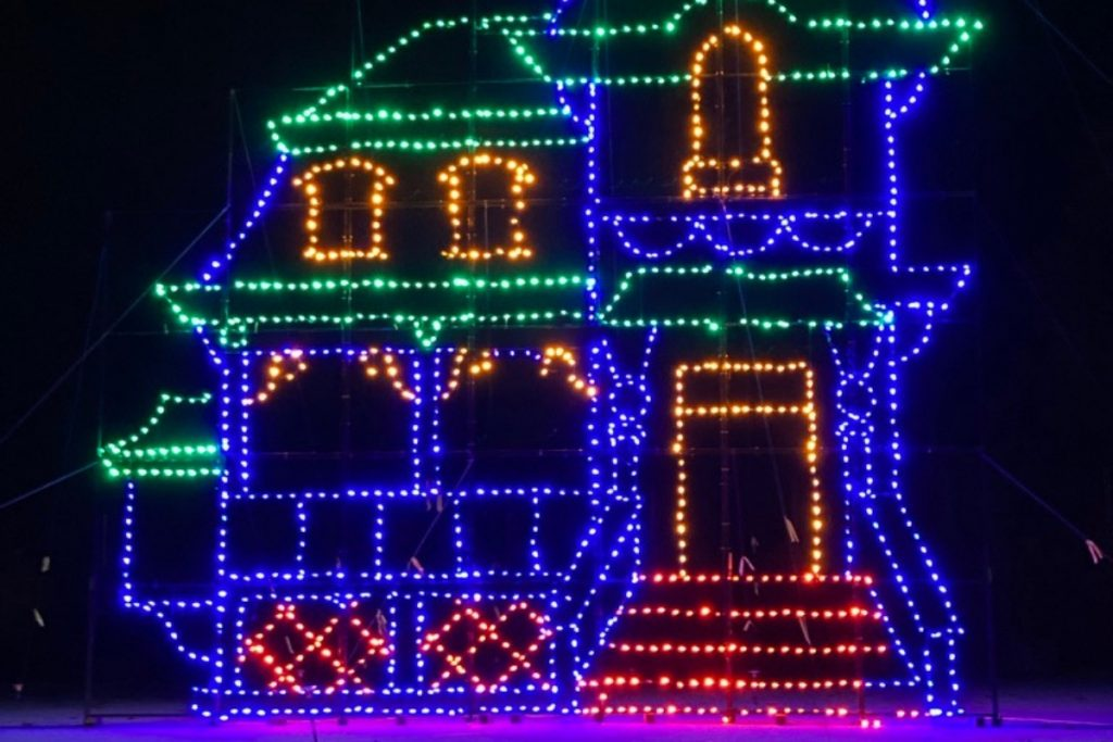 At night, the outline of a home in blue and green and red Christmas lights.