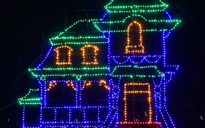 At night a lit up house oulined in Christmas lights