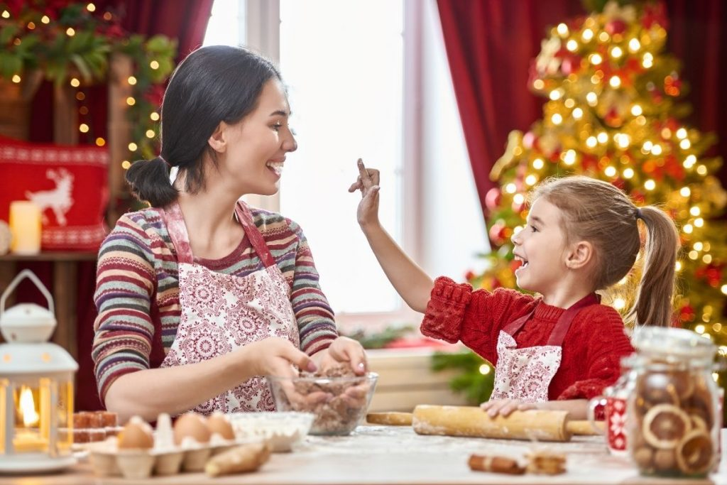 Mom and daughter laughing as they decorate cookies at Christmas time