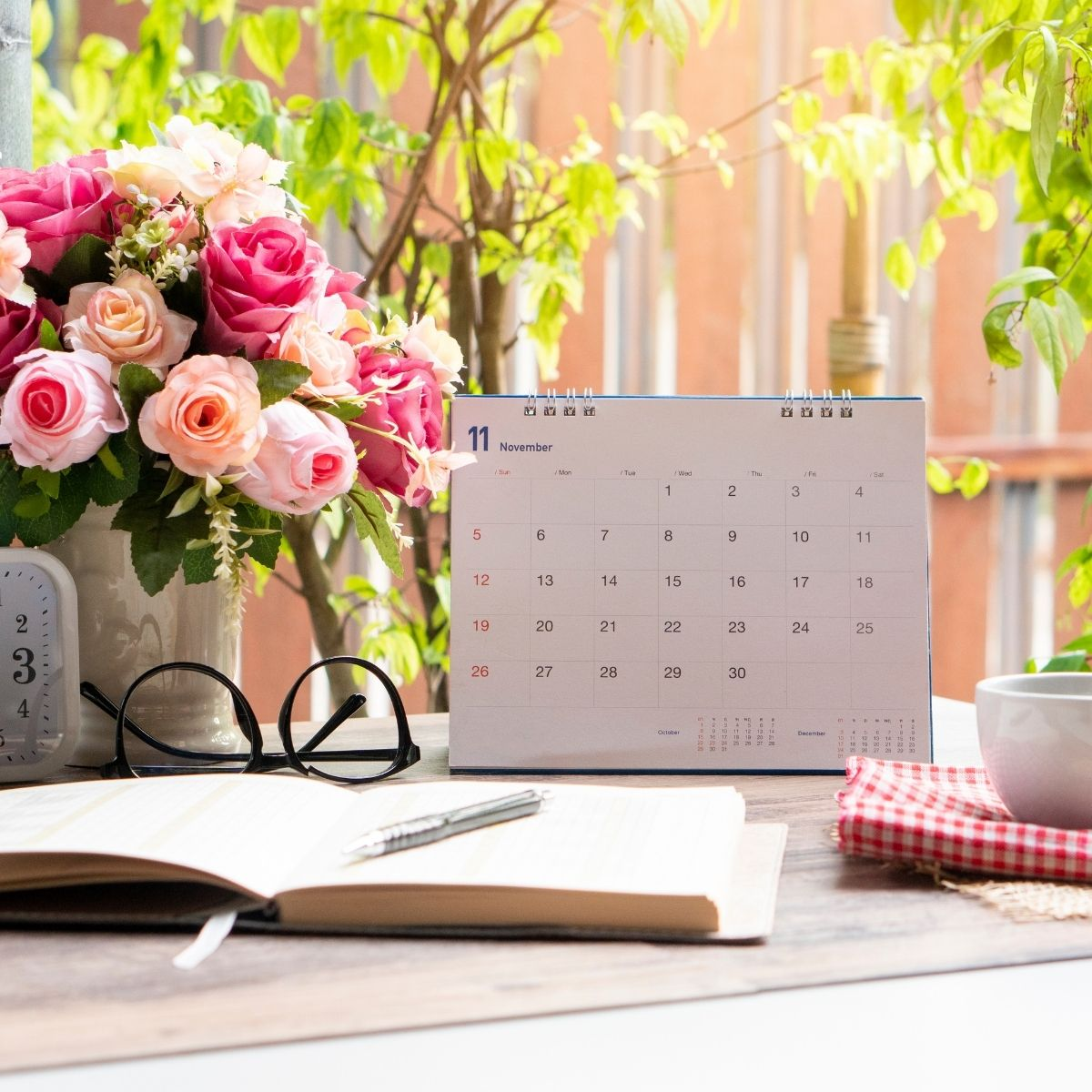 a jouranl, vase of flowers and a blank calendar on a table