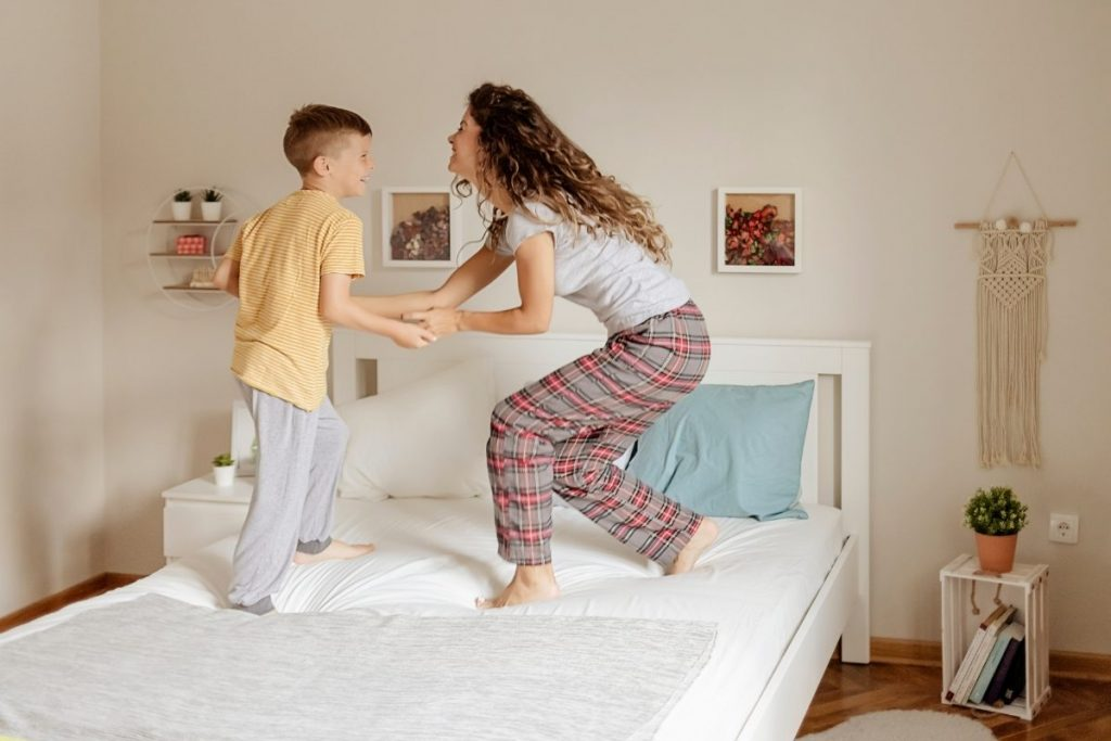Mom and son happy dance on a bed