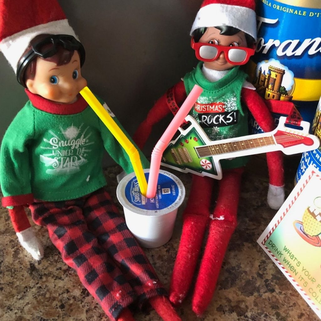 Two Christmas elves drinking hot cocoa from a straw