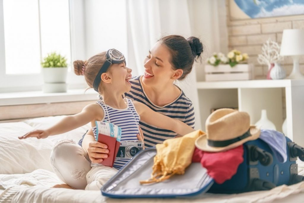mom and daughter happy as they pack a suitcase for a trip