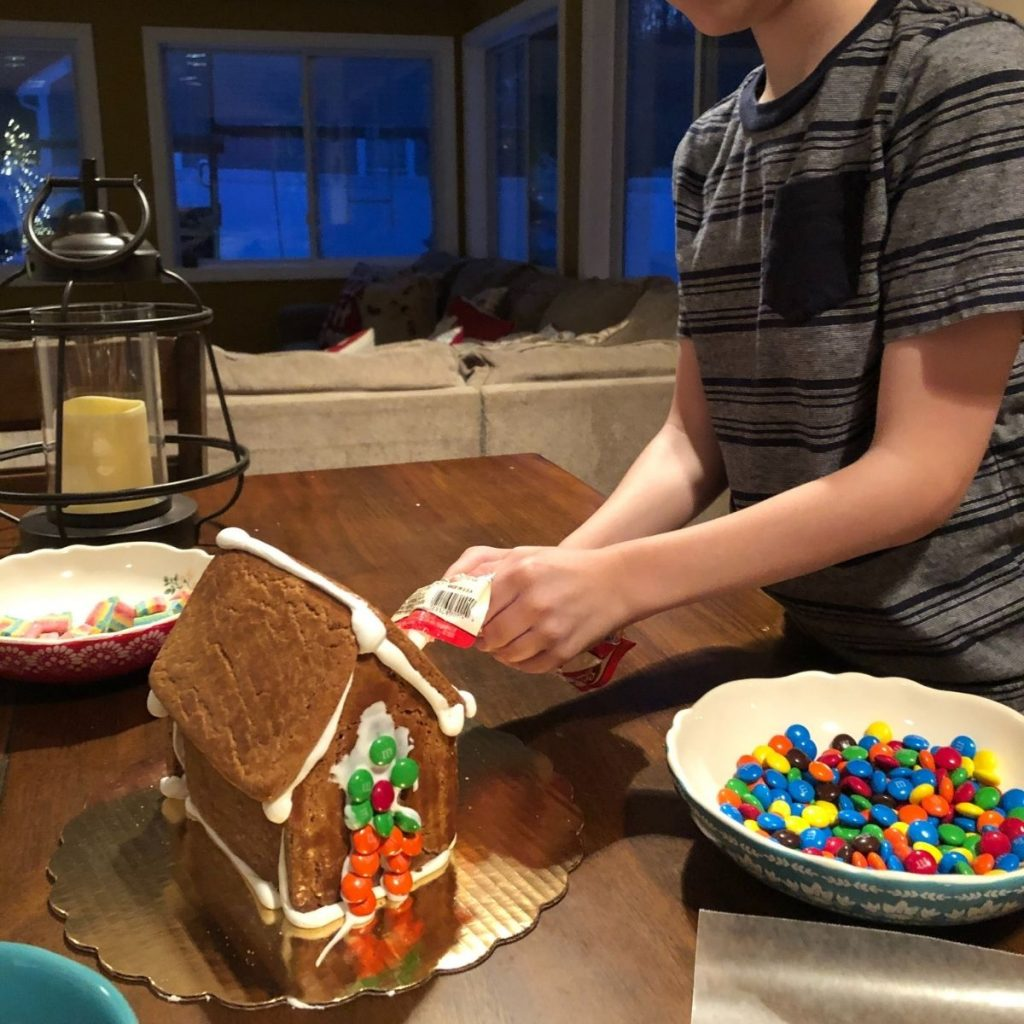boy decorating a gingerbread house with candies and frosting