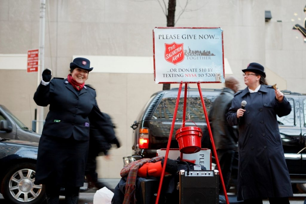 Two women being Salvation Army bell ringers outdoors