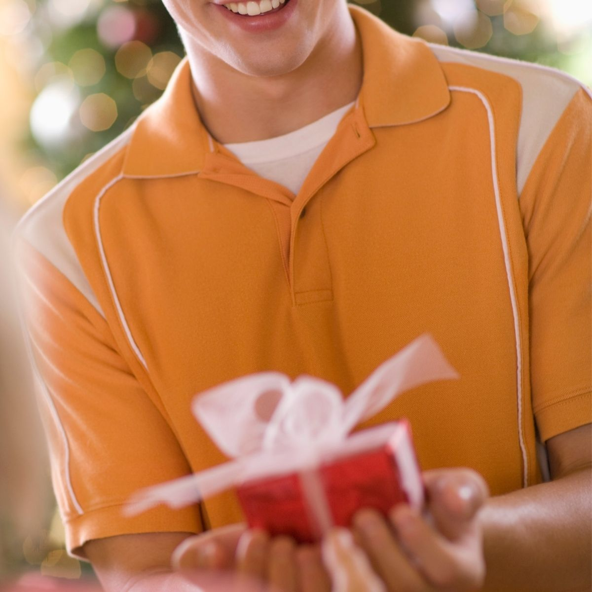 A teen boy holing a wrapped gift in his hands