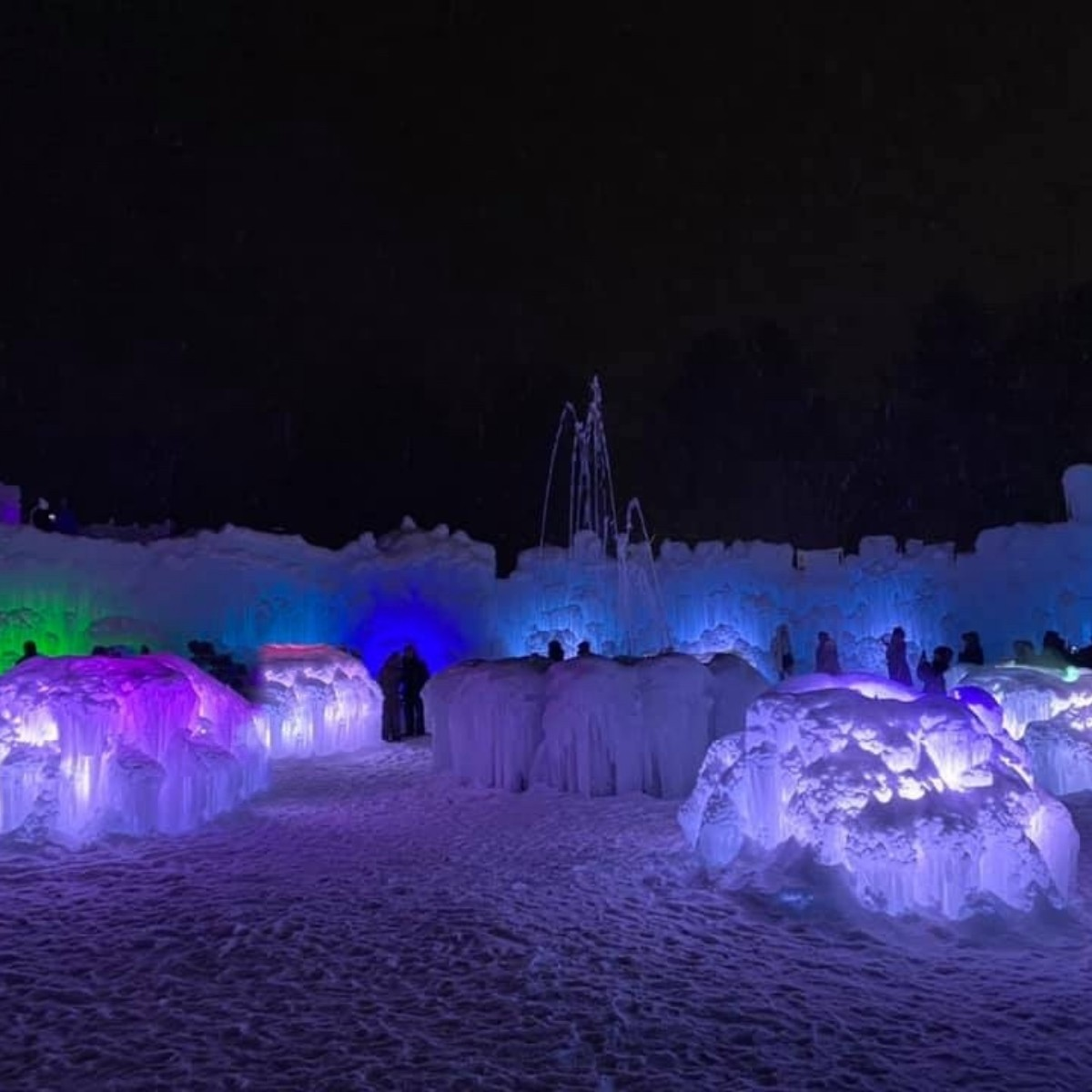The Ice Castles at night all aglow in purples and blues.