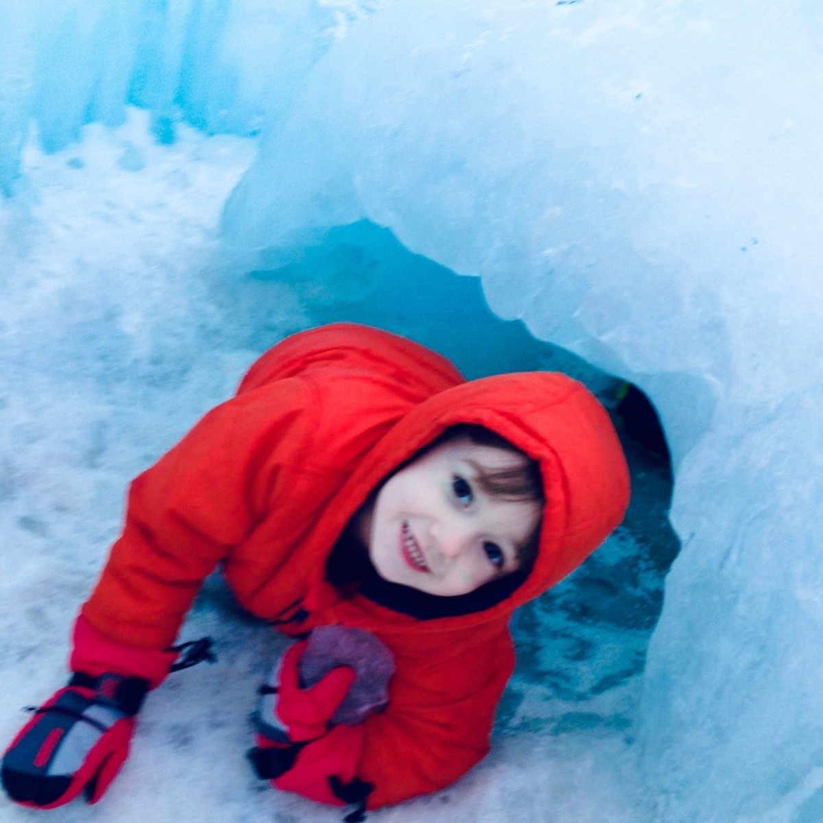 A young boy crawls through one of the many ice tunnel at the North Woodstock, NH Ice Castles.