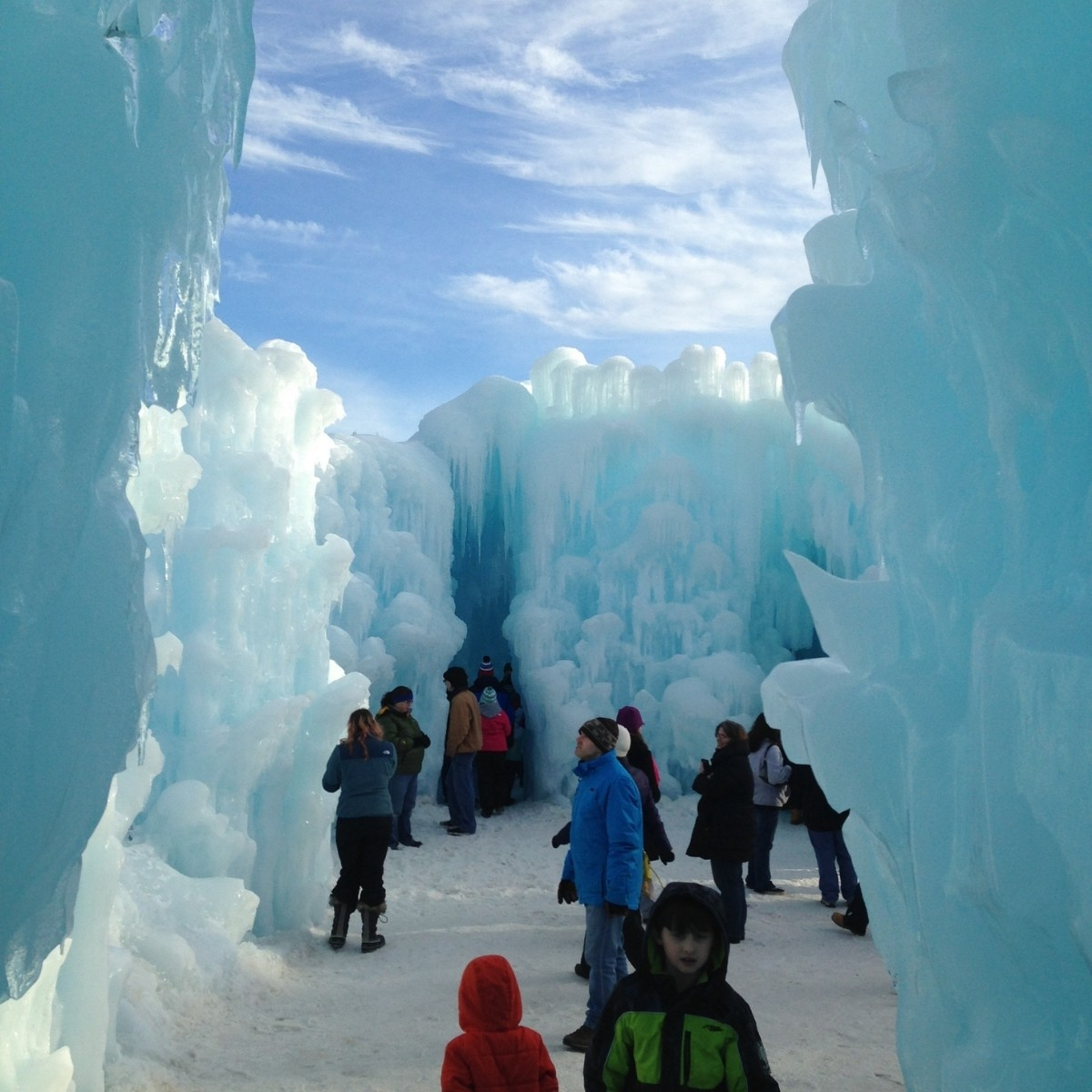 Tall walls of ice at the Ice Castles in New Hampshire with people walking around.