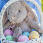 A white basket filled with Easter eggs and an plush bunny toy.